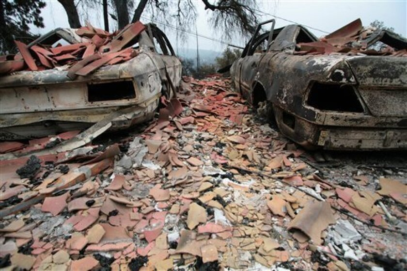 The charred hulls of two Mercedes cars are seen on Sunday, May 10, 2009, after flames from a wind-driven wildfire ravaged a home along Holly Road in the Mission Canyon area of Santa Barbara, Calif. (AP Photo/ Eric Parsons)