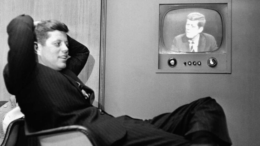 Then-presidential candidate John F. Kennedy watches a playback of his televised appearance in Wisconsin on April 3, 1960.