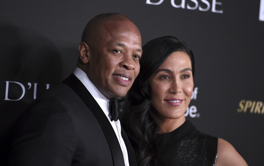 FILE - In a Thursday, Oct. 11, 2018 file photo, Dr. Dre, left, and Nicole Young arrive at the City of Hope Gala, at the Barker Hangar in Santa Monica, Calif. Dr. Dre's wife of 24 years Nicole Young has filed for divorce. Young filed documents Monday, June 29, 2020 seeking to end her marriage with the producer, rapper and music mogul whose real name is Andre Young in Los Angeles Superior Court.(Photo by Jordan Strauss/Invision/AP, File)