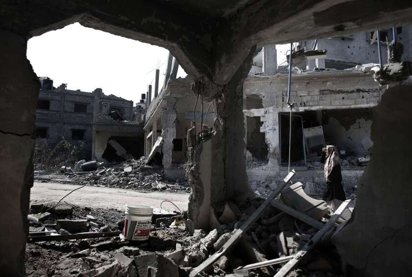 A Palestinian woman walks past destroyed buildings in the northern Gaza Strip city of Beit Hanun.