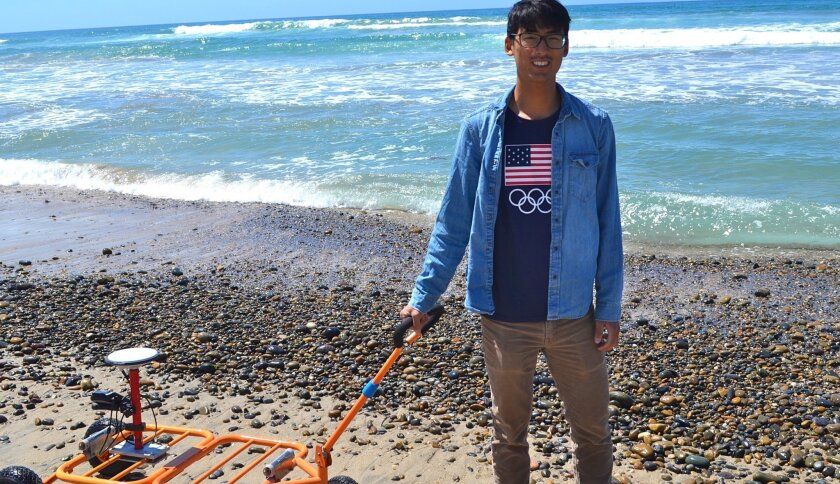 At Moonlight Beach, city of Encinitas intern Sean Lee drags surveying equipment that captures sand levels. Encinitas is tracking sand movement, which will inform future beach replenishments.