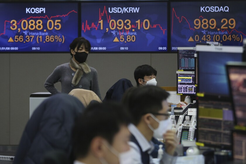 A currency trader walks by the screens showing the Korea Composite Stock Price Index (KOSPI), left, and the foreign exchange rate between U.S. dollar and South Korean won at the foreign exchange dealing room of the KEB Hana Bank headquarters in Seoul, South Korea, Friday, Jan. 8, 2021. Asian shares mostly rose Friday on hopes for additional economic stimulus after U.S. Congress confirmed Joe Biden as the winner of the presidential election. (AP Photo/Ahn Young-joon)