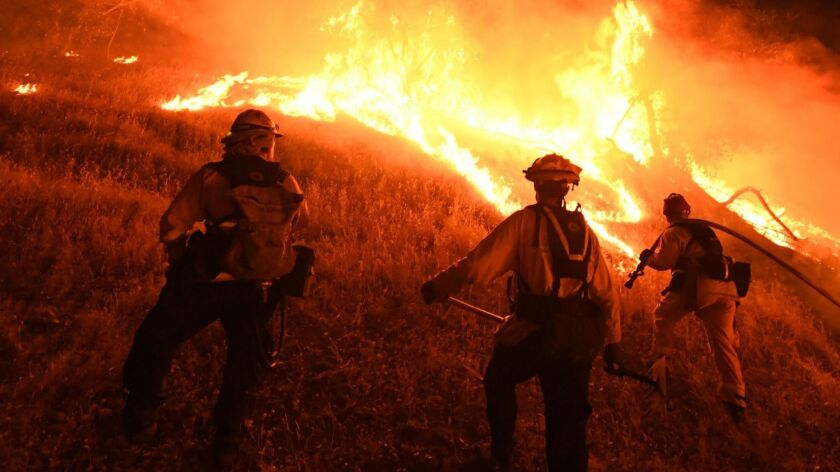 Firefighters conduct a controlled burn to defend houses against flames from the Ranch fire, part of the Mendocino Complex fire, as it spread toward the town of Upper Lake, Calif.