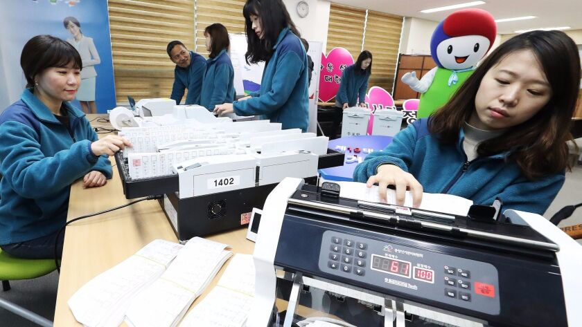 Officials at a local election management committee check voting machines to prepare for the upcoming presidential election in Suwon, South Korea, on March 12.