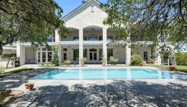 The 2.6-acre estate holds a 9,600-square-foot home, a grassy yard with a pool and a 600-square-foot stone wine cellar.
