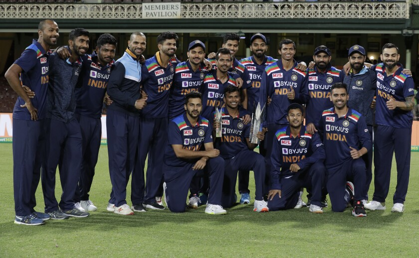 Members of the Indian team pose with the winners trophy at the end of the third T20 international cricket match between Australia and India at the Sydney Cricket Ground in Sydney, Australia, Tuesday, Dec. 8, 2020. Indian won the series 2-1. (AP Photo/Rick Rycroft)