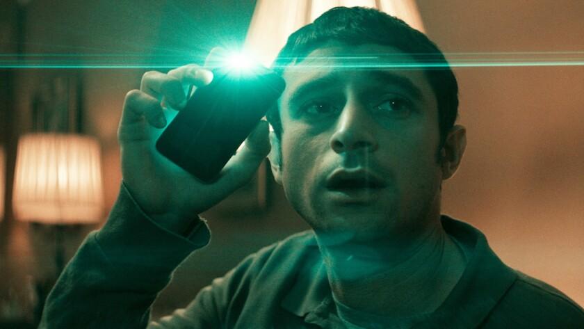"Dave Davis holds up a cellphone flashlight in ""The Vigil."""
