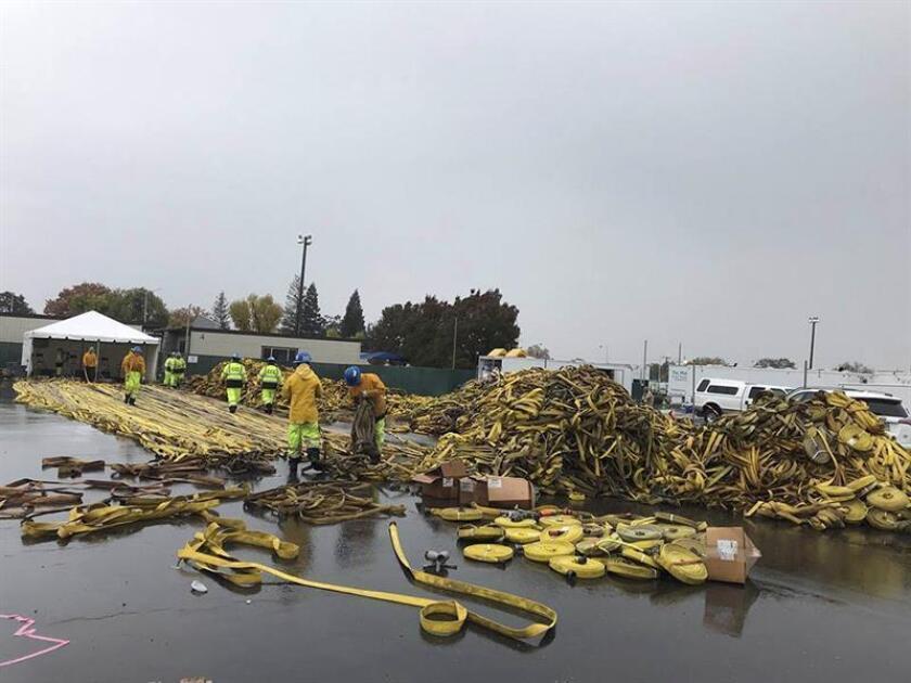 Fotografía cedida por los Bomberos del Condado de Butte que muestra a bomberos y el Cuerpo de Conservación de California mientras limpian y organizan las mangueras que se utilizaron en el incendio, mientras cae una lluvia constante hoy en el Condado de Butte, California (EE.UU.). EFE/Cortesía Bomberos Del Condado De Butte