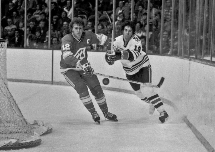 FILE - In this Dec. 18, 1977, file photo, Atlanta Flames' Tom Lysiak, left, and Chicago Blackhawks' Dale Tallon chase after the puck during the first period of an NHL hockey game in Chicago. Lysiak, a three-time NHL All-Star who played 13 NHL seasons with the Flames and Blackhawks, has died of leuk