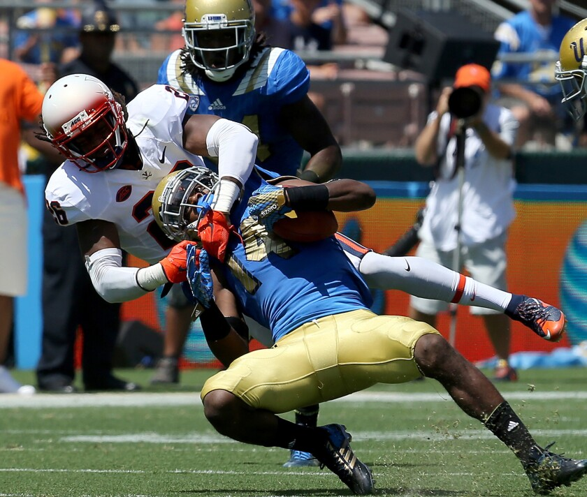 UCLA receiver Mossi Johnson hauls in a pass against the defense of Virginia cornerback Maurice Canady in the first half Saturday afternoon at the Rose Bowl.