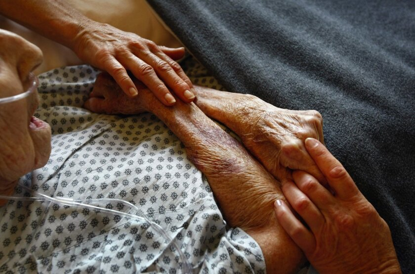 Hospice volunteers in Lakewood, Colo., caress the hands of a terminally ill patient.