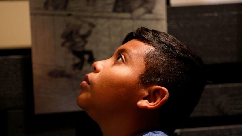 Fernando Quiroz, 11, a student at Southeast Middle School, takes in an exhibit at La Plaza de Cultur