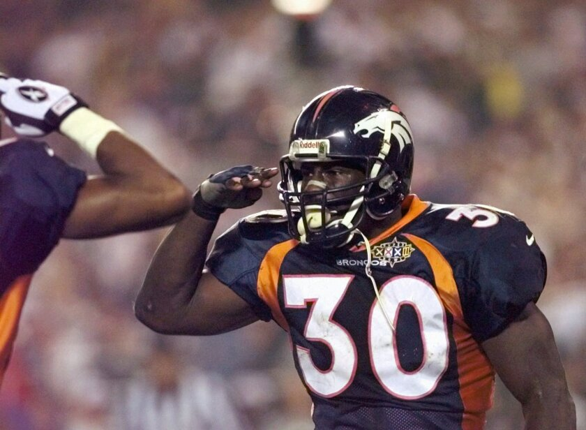 FILE - In this Jan. 25, 1998, file photo, Denver Broncos running back Terrell Davis salutes after his third quarter touchdown during Super Bowl XXXII at San Diego's Qualcomm Stadium Sunday, Jan. 25, 1998. Davis rushed for 157 yards and a record three touchdowns to lead the Broncos to their first NFL title and break the NFC's streak of 13 consecutive Super Bowl victories. (AP Photo/Ed Reinke, File)