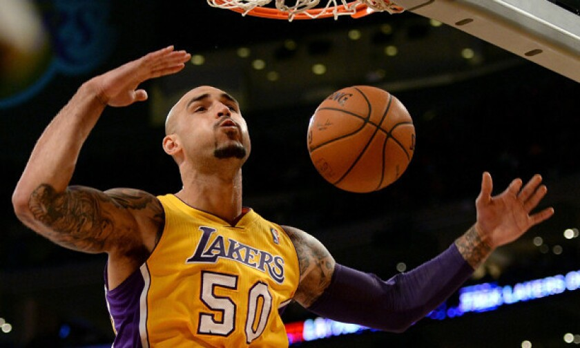 Lakers center Robert Sacre dunks during a win over the New York Knicks on Tuesday. Sacre is staying positive about his future and whether it involves the Lakers after this season.
