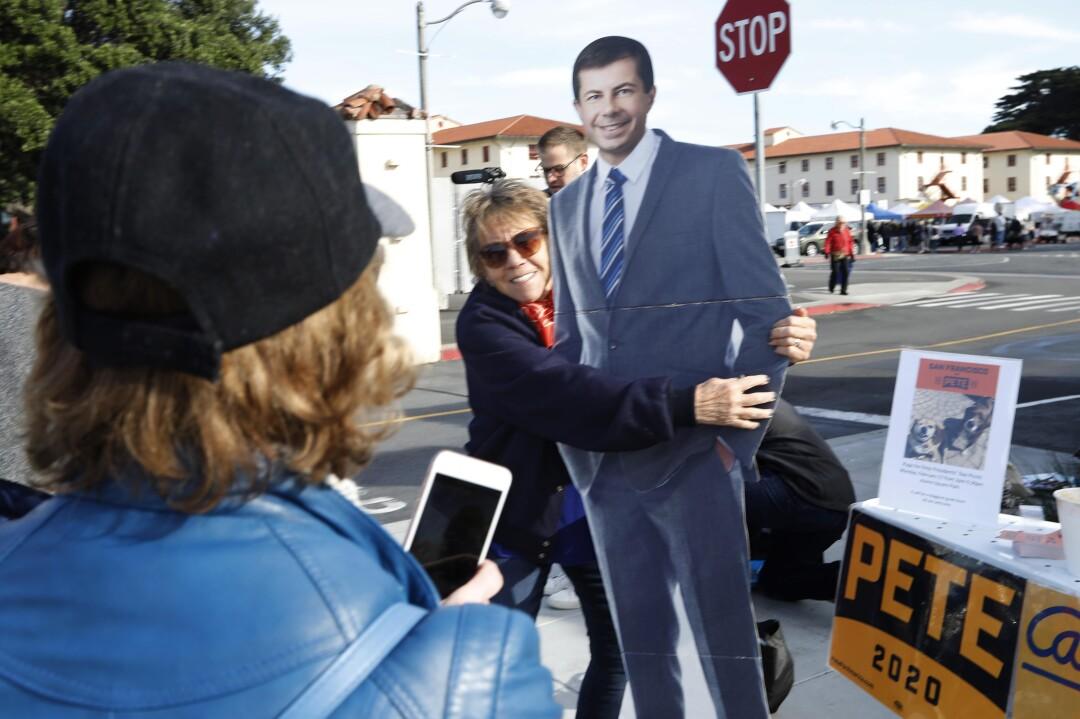 People pose with a cardboard cutout of Pete Buttigieg near the Fort Mason farmers market