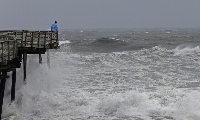 An onlooker checks out the heavy surf at the Avalon Fishing Pier in Kill Devil Hills, N.C., Thursday, Sept. 13, 2018 as Hurricane Florence approaches the east coast.