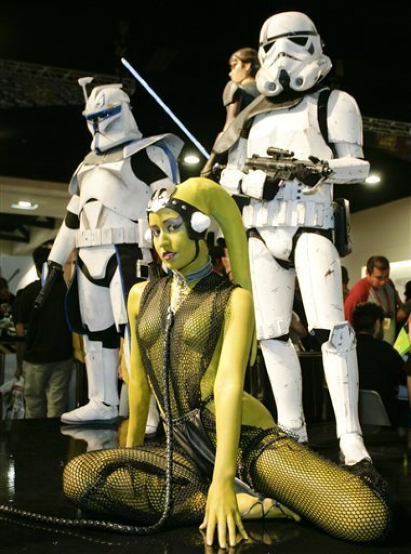 Victoria Schmidt, foreground, dressed as Oola from Star Wars poses with other fans at Comic-Con International 2009 convention held in San Diego Friday, July 24, 2009. The annual comic book and popular arts convention attracts over 100,000 people and runs through Sunday July 26.  (AP Photo/Denis Por
