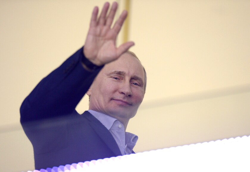 Russian President Vladimir Putin waves during the Men's Ice Hockey Group A match of the USA vs. Russia at the Bolshoy Ice Dome during the Sochi Winter Olympics on February 15, 2014, in Sochi.