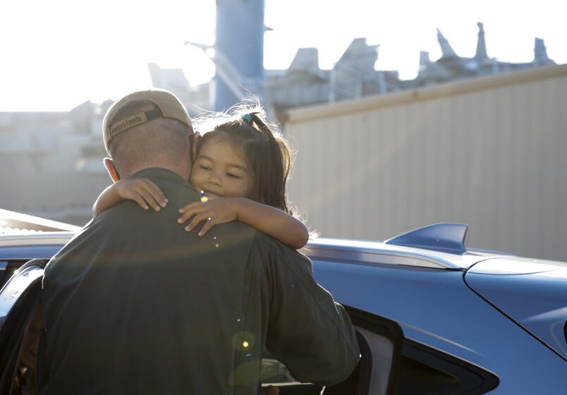 Chief Warrant Officer Hadley Dykes, 37, with the aircraft carrier Carl Vinson says goodbye to his daughter, Luna, 3.