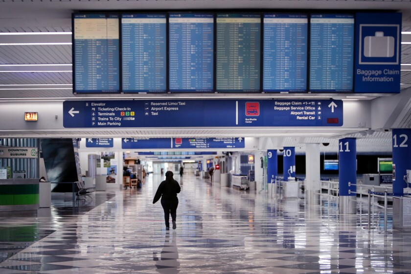 A worker walks through a baggage claim area at a nearly-empty O'Hare International Airport Chicago in April.