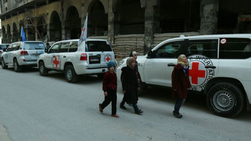 Syrian children walk past vehicles of the U.N. and the International Committee of the Red Cross delivering humanitarian aid in the Syrian town of Duma on the eastern outskirts of the capital, Damascus, on Friday.