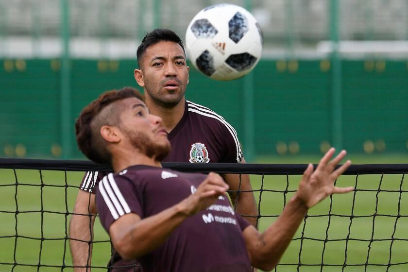 Jonathan Dos Santos controla un balón, ante la mirada de Marco Fabián, en la sesión del Tri.
