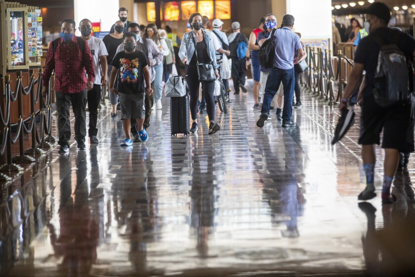 People wearing masks walk through Union Station in Los Angeles.