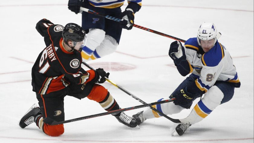 Ducks' Troy Terry, left, shoots under defense by St. Louis Blues' Tyler Bozak during the third period.