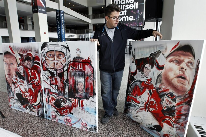 Artist David Arrigo carries three of his paintings of former New Jersey Devils goalie Martin Brodeur, Tuesday, Feb. 9, 2016, at the Prudential Center arena in Newark, N.J. Two of the paintings will be auctioned for charity and one will go to Brodeur. The Devils will retire Brodeur's number 30 jerse