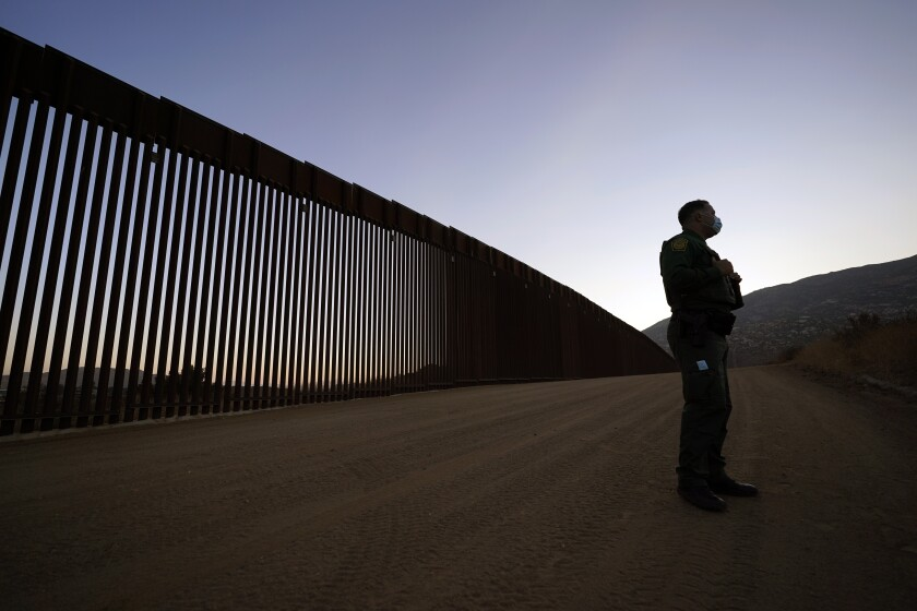 Border Patrol agent Justin Castrejon in front of newly replaced border wall sections