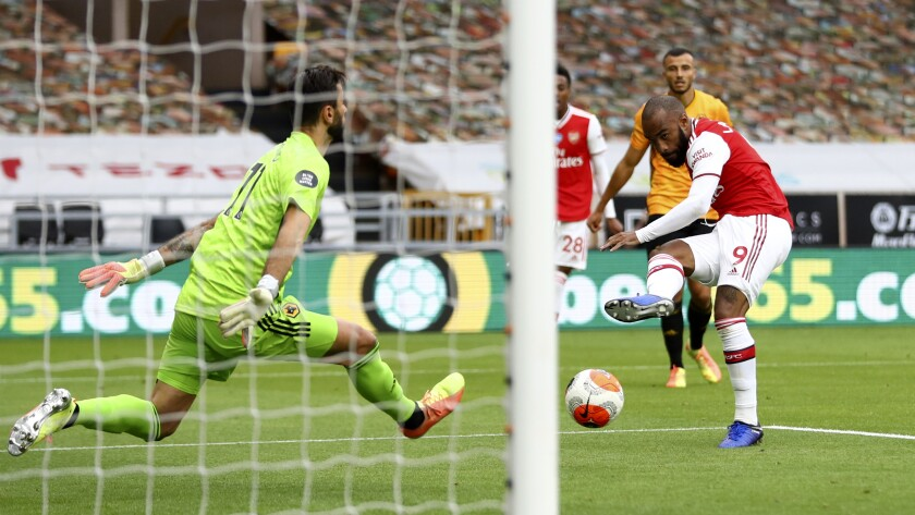 Arsenal's Alexandre Lacazette scores his side's second goal past Wolverhampton Wanderers' goalkeeper Rui Patricio, left, during the English Premier League soccer match between Wolverhampton Wanderers and Arsenal at the Molineux Stadium in Wolverhampton, England, Saturday, July 4, 2020. (Michael Steele/Pool via AP)