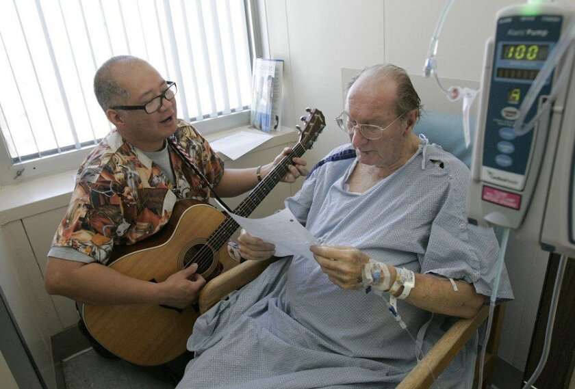 Nurse Rod Salaysay serenades a patient, Harry W. Crocker, at Scripps Memorial Hospital.