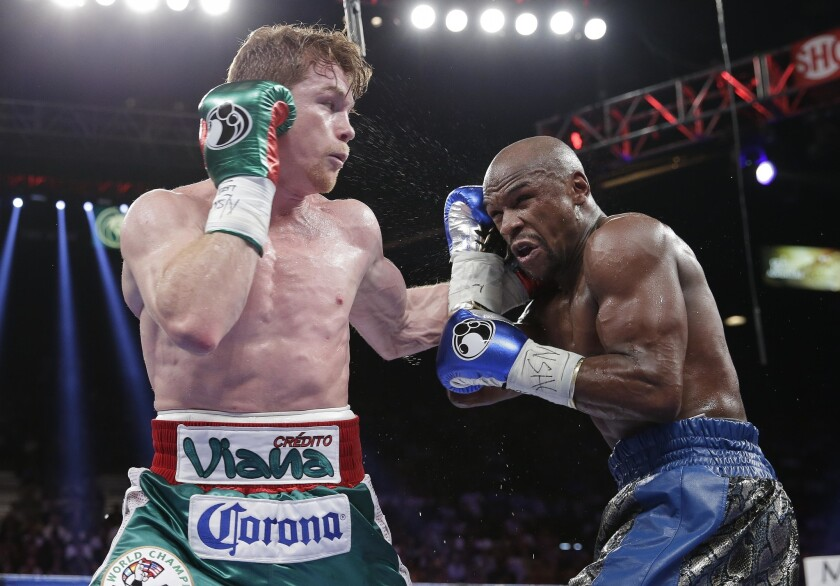 Canelo Alvarez lands a jab against Floyd Mayweather Jr. in the third round during a 152-pound title fight, Saturday, Sept. 14, 2013, in Las Vegas.