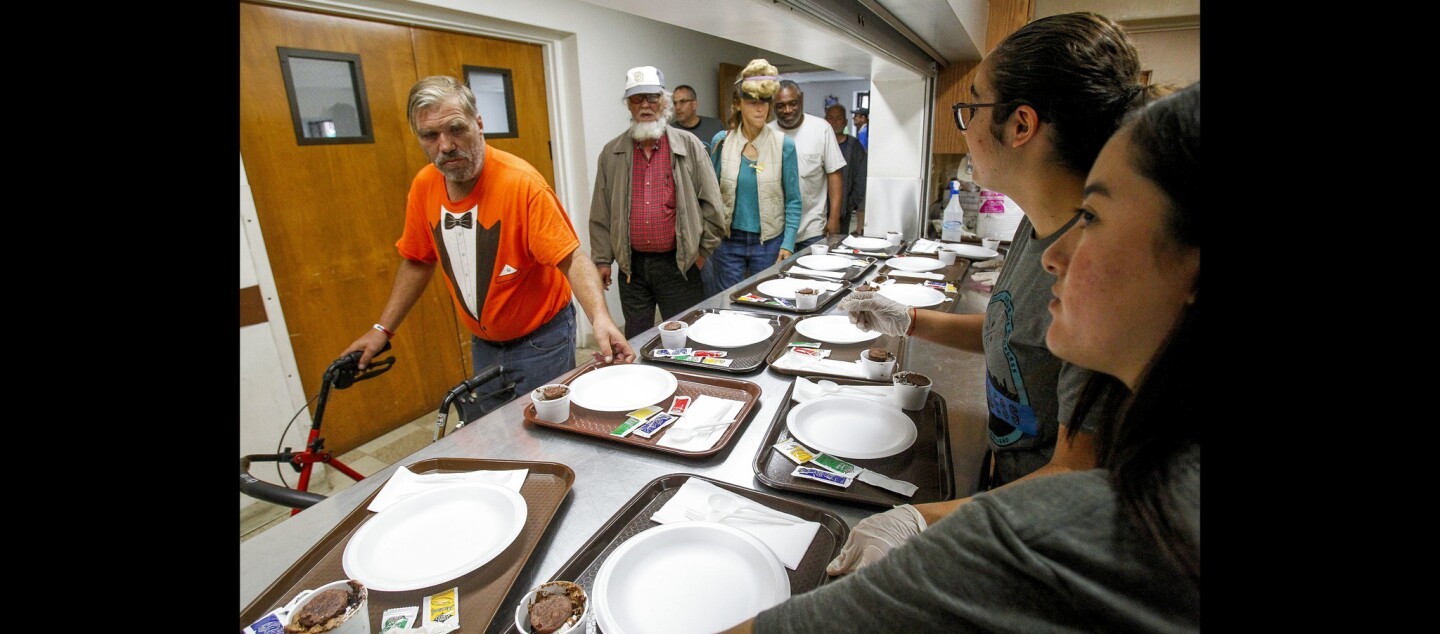 Mater Dei Catholic High School students Gretta Ochoa, 15, second from right, and Galia Santana, 14, far right, give trays with plates to people, many of them homeless, as they receive a lunch during the 35th birthday celebration for the Ladle Fellowship.