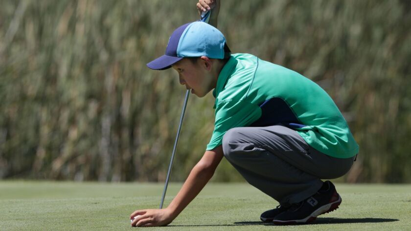 At the IMG Academy Junior Golf World Championships, Jay Leng, Jr. place his ball back down on the 17th green.