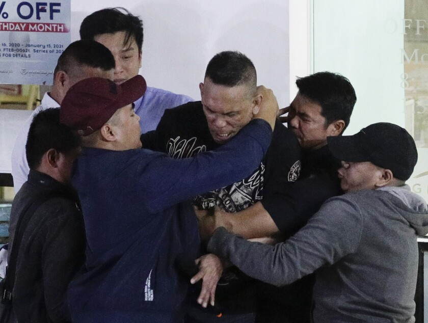 Former security guard Alchie Paray is restrained by police as he talks to media after releasing all his hostages at the V-mall in Manila, Philippines on Monday, March 2, 2020. Officials say a recently dismissed security guard has released his hostages and walked out of a Philippine shopping mall, ending a daylong hostage crisis.(AP Photo/Aaron Favila)