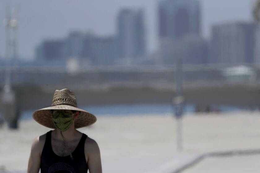 A man wears a mask and wide-brimmed hat as he walks along Junipero Beach in Long Beach on June 11.