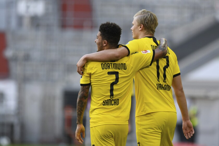 Dortmund's Erling Haaland, right, celebrates the opening goal with his team mate Jadon Sancho during the German Bundesliga soccer match between Fortuna Duesseldorf and Borussia Dortmund in Duesseldorf, Germany, Saturday, June 13, 2020. Because of the coronavirus outbreak all soccer matches of the German Bundesliga take place without spectators. (Bernd Thissen/Pool via AP)