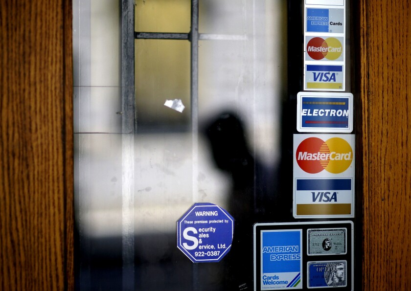 FILE - In this July 18, 2012, file photo, credit card logos are seen on a downtown storefront as a pedestrian passes in Atlanta. The coronavirus pandemic has made financial security a higher priority than ever. If you're in a stable position now, you can increase future flexibility by reducing credit card debt. (AP Photo/David Goldman, File)