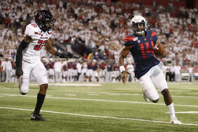 Arizona quarterback Khalil Tate runs past Texas Tech cornerback Ja'Marcus Ingram during the second half on Sept. 14 in Tucson.