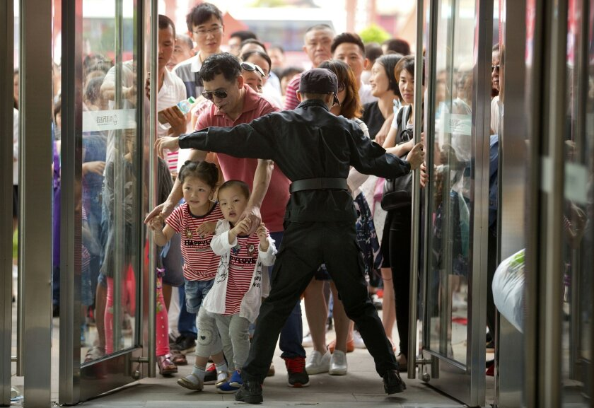 A security guard opens the entrance doors for the grand opening of the Wanda Mall at the Wanda Cultural Tourism City in Nanchang in southeastern China's Jiangxi province, Saturday, May 28, 2016. China's largest private property developer, the Wanda Group, opened an entertainment complex on Saturday