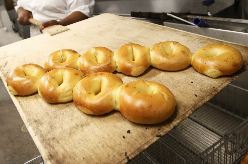 Baker Sharelle Robbins removes a pastry mat laden with egg bagels fresh from the oven at Kossar's Bagels and Bialys in New York on Thursday, May 26, 2016. At street carts and bodegas, diners and supermarkets, nowhere is the bagel more ubiquitous than New York City. (AP Photo/Kathy Willens)