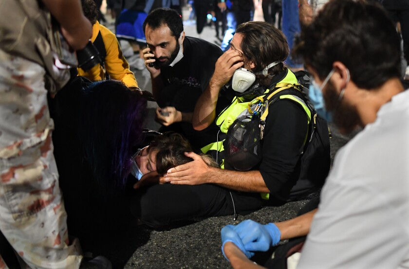 Paramedics help a protester who was hit by a vehicle on Sunset Boulevard in Hollywood. (Los Angeles Times/Wally Skalij)