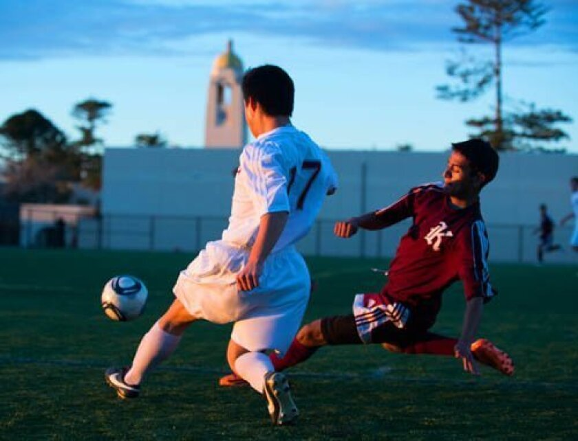 Sophomore Jihadi Chang (17) of Bishop's passes the ball in second half action against Kearny Dec. 10 with a backdrop of The Bishop's School tower. Photos Ed Piper