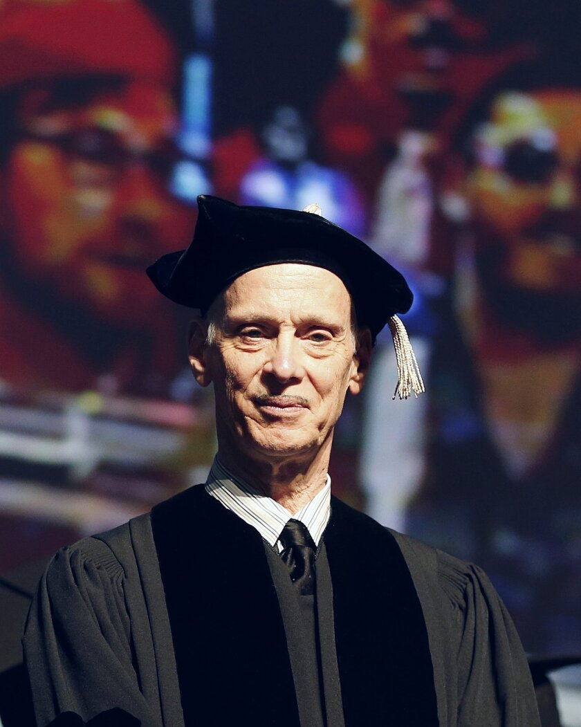 John Waters stands on the dais in front of a video screen projection of a marching band before receiving an honorary doctor of Fine Arts degree from Rhode Island School of Design during commencement ceremonies in Providence, R.I., Saturday, May 30 2015. (AP Photo/Michael Dwyer)