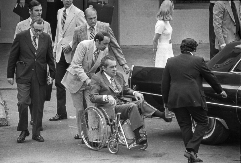 Oct. 4, 1974: Secret Service agents, aides and hospital personnel help former President Nixon into limousine for departure from a Long Beach hospital.
