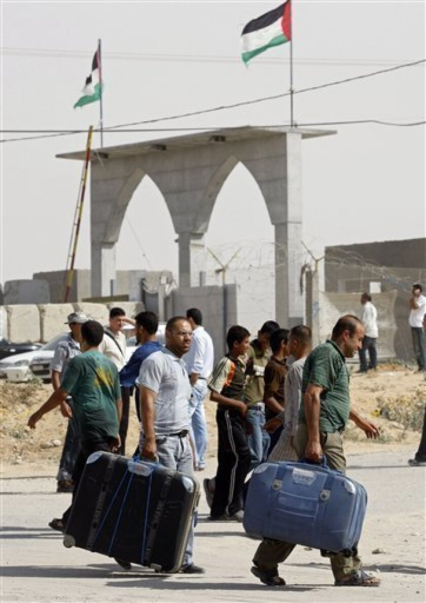 Palestinians carry suitcases before crossing into Egypt through the Rafah border crossing, southern Gaza Strip, Tuesday, June 1, 2010. An Egyptian official says the government is temporarily lifting its blockade of the Gaza Strip to allow aid into the area a day after Israel raided an international