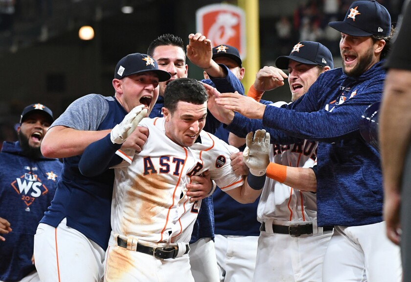 HOUSTON, TEXAS OCTOBER 29, 2017-Astros Alex Bregman is mobbed by teammates after hitting the game winner against the Dodgers in the 10th inning in Game 5 of the World Series at Minute Maid Park in Houston Sunday. (Wally Skalij/Los Angeles Times)