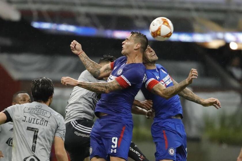 Los jugadores Milton Caraglio (c) y Edgar Mendez (d) de Cruz Azul disputan el balón con Andrés Andrade (i) de Atlas, durante el juego correspondiente a la décima jornada del torneo mexicano de fútbol celebrado en el estadio Azteca de Ciudad de México (México). EFE
