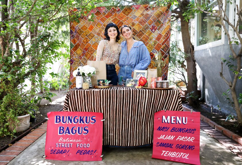 """Two women stand at a reception table behind a sign that announces """"Bungkus Bagus: Balinese Street Food."""""""